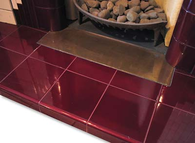 Hearth in 6 inch Burgundy tiles with a brass heat plate